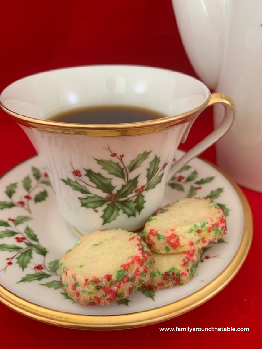 Butter cookies on a saucer with coffee cup.