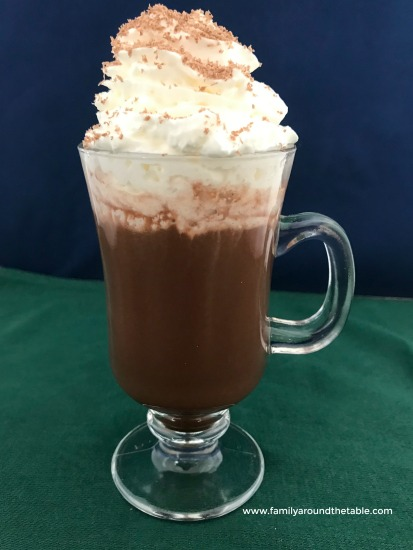 A mug of hot chocolate topped with whipped cream and chocolate shavings.