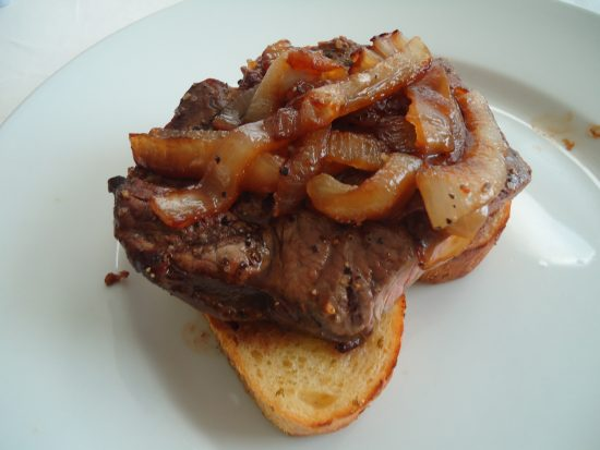 Open-faced steak and onions on garlic toast