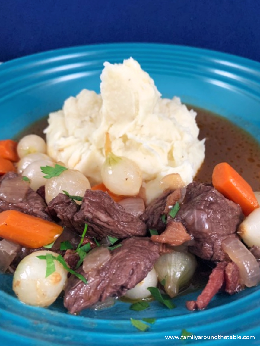Beef bourguignon and mashed potatoes on a blue plate.
