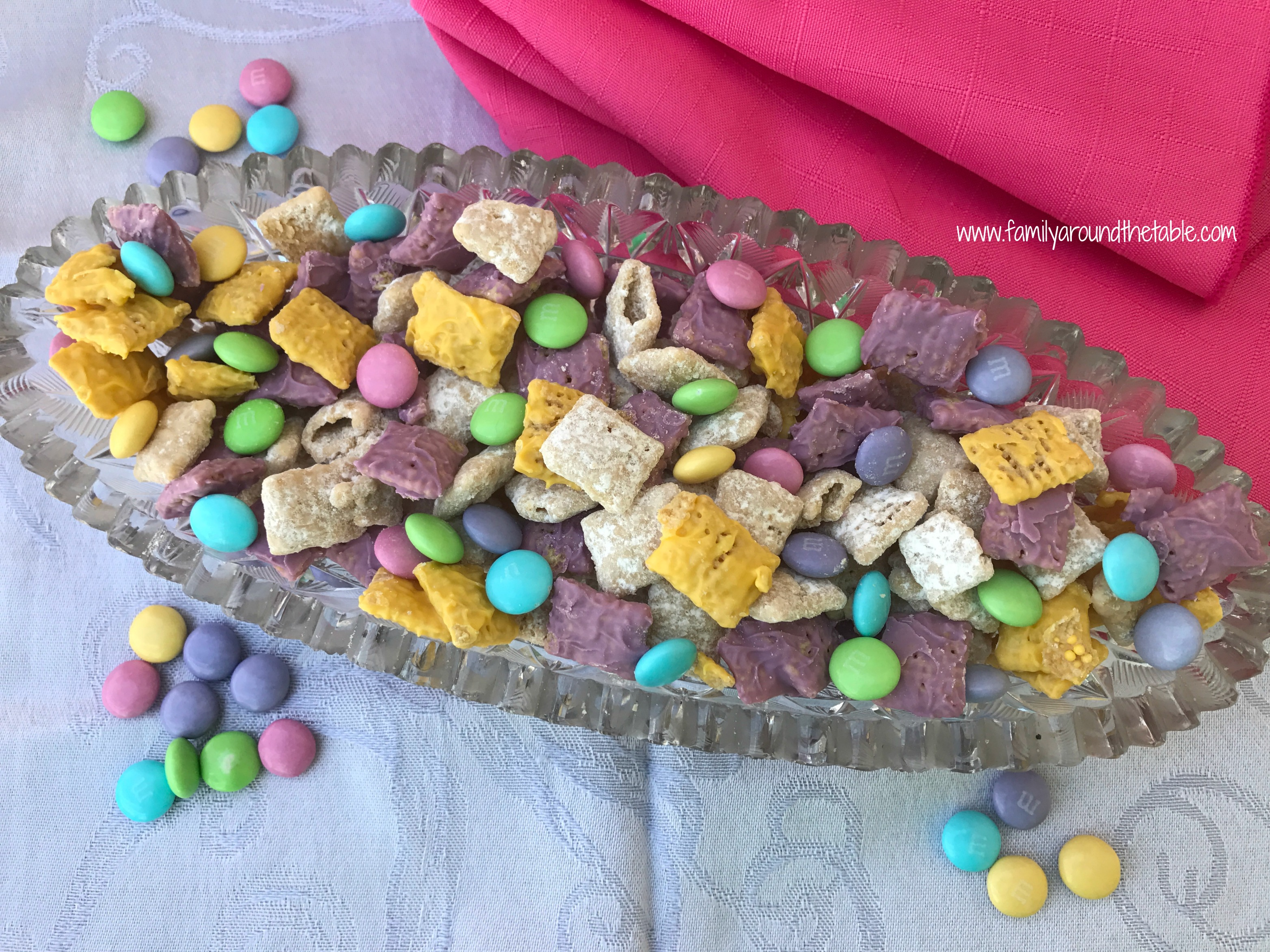 Overhead photo of Easter Muddy Buddies in a glass serving dish with a pink cloth next to it.