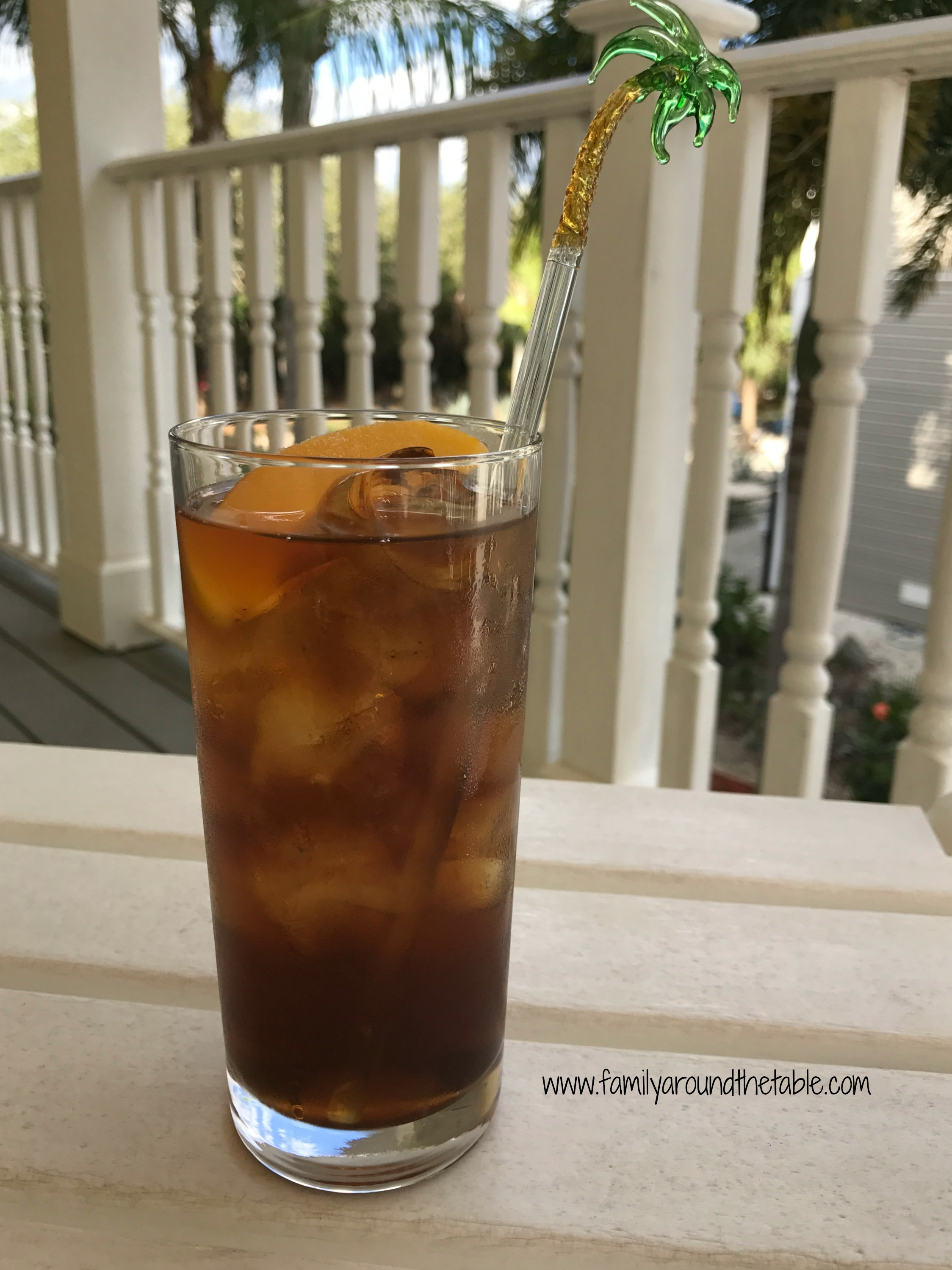 A glass of bourbon peach tea on a table outside.