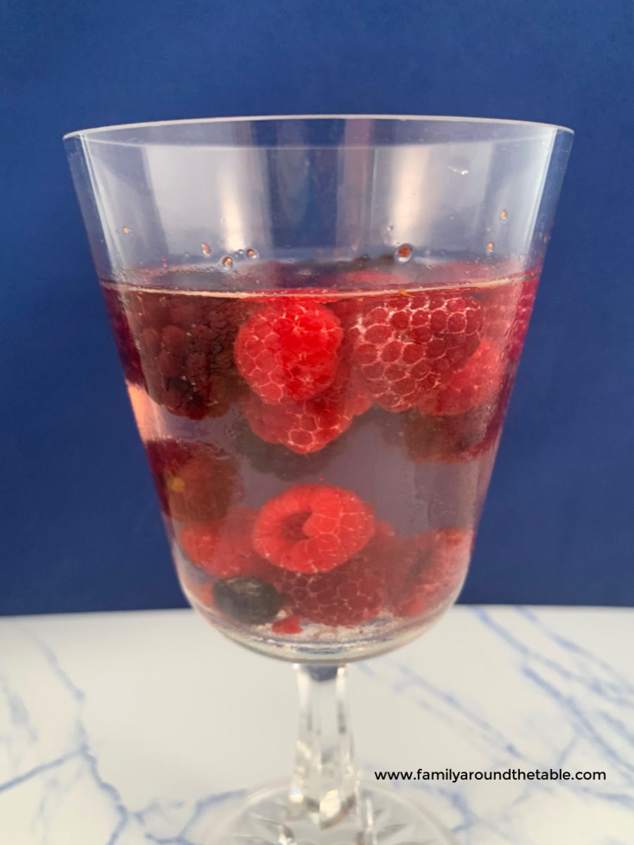 Mixed berry sangria in a wine glass with berries.