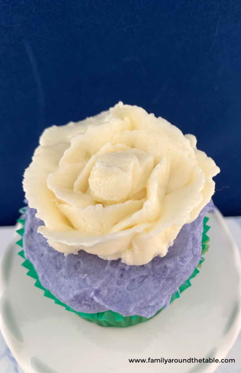 White chocolate buttercream rose on lavender frosting on a cupcake.
