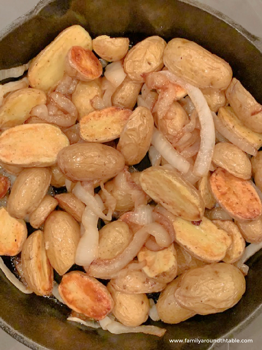 Roasted potatoes and onions in a skillet.