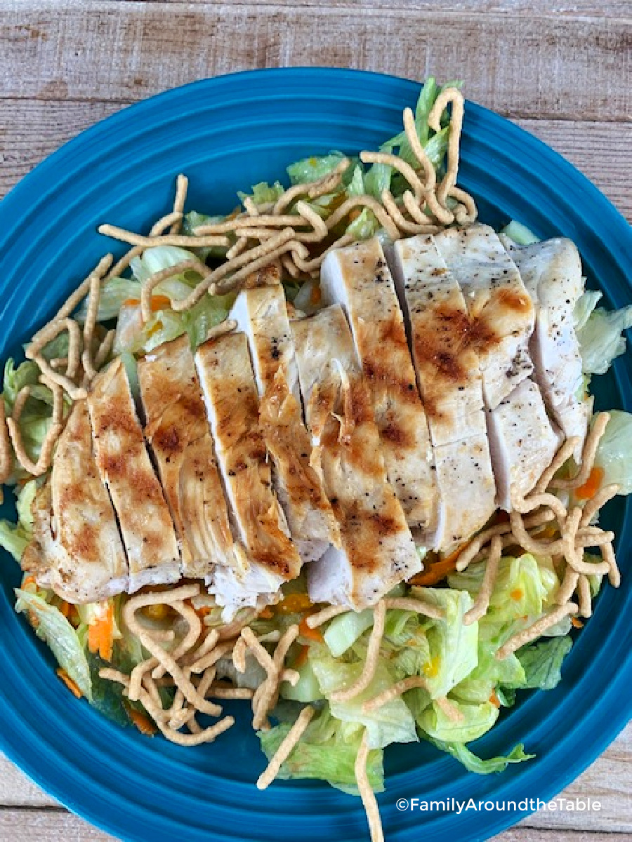 A sliced chicken breast on a salad.