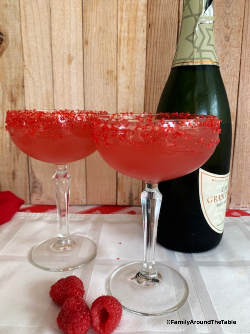 Two coupe glasses filled with a pink flirtini cocktail with a bottle fo sparkling wine in the background.