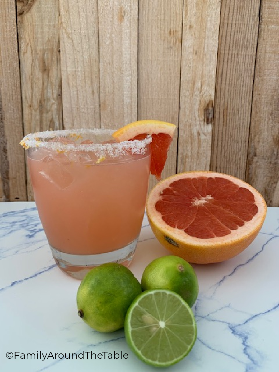 A cocktail glass next to limes and a ruby red grapefruit.