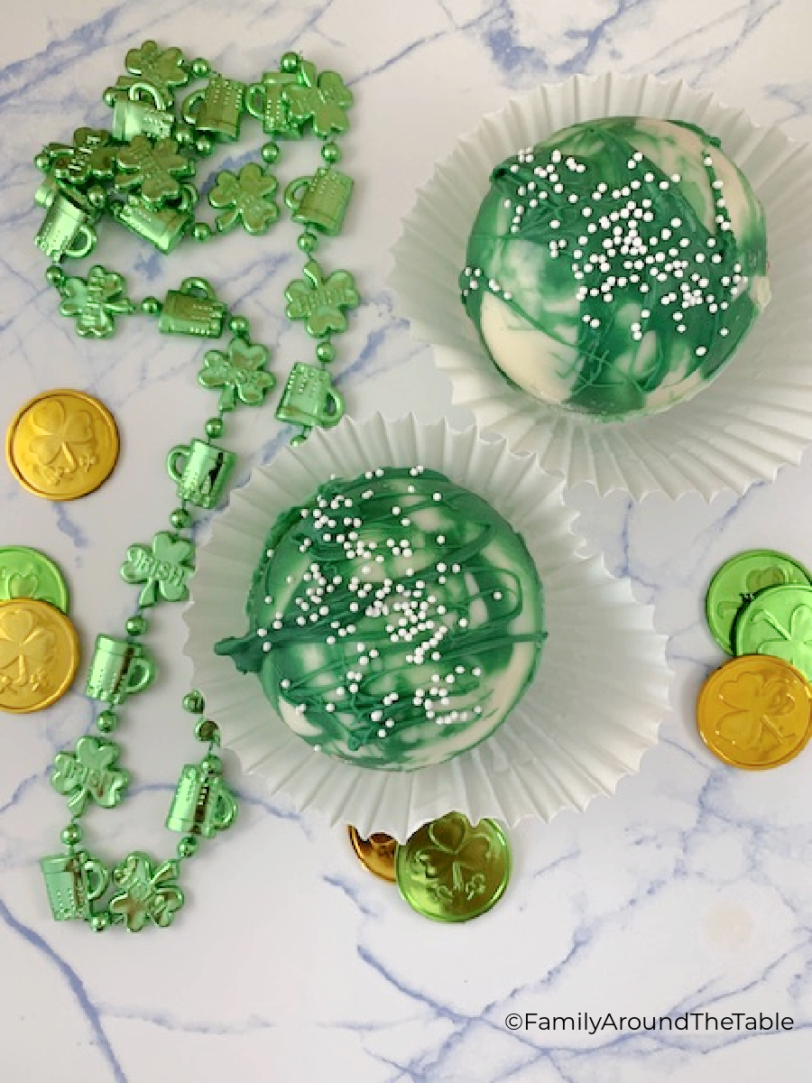 Overhead photo of St. Patrick's Day Cocoa Bombs with beads and coins around them.